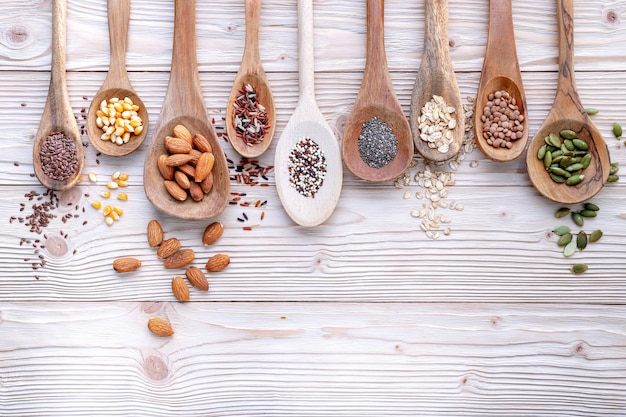 Different types of grains and cereals on shabby wooden background.