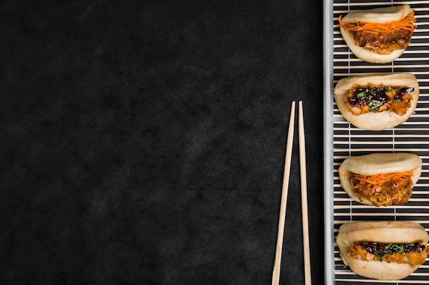 Different types of gua bao on placemat with chopsticks against black textured backdrop