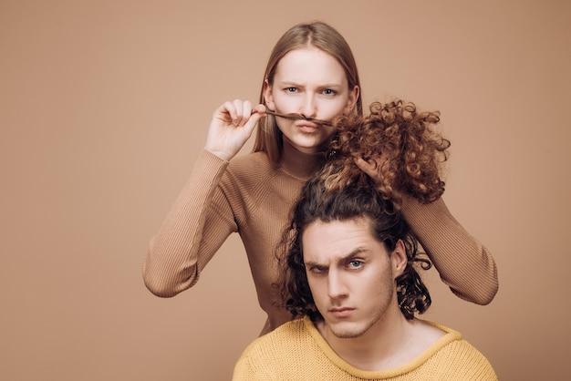 Different types of hair concept. happy couple in love studio photo. handsome man with long wavy hair and his cute girlfriend. beautiful girl playing with her boyfriend hair.