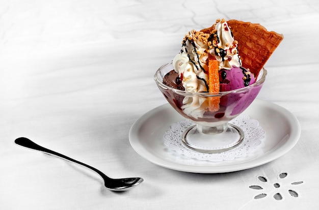 Different types of ice cream with nuts, orange, chocolate and vanilla in a glass cup.