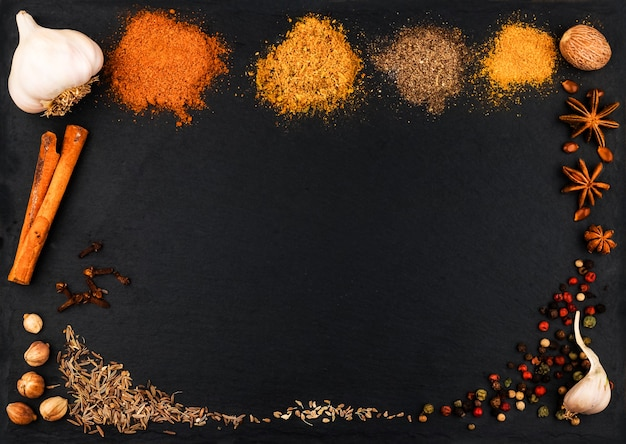 Different types of indian colorful spice and spices on a dark stone background