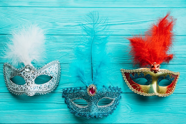 Different types of masquerade carnival mask with feather on blue wooden table