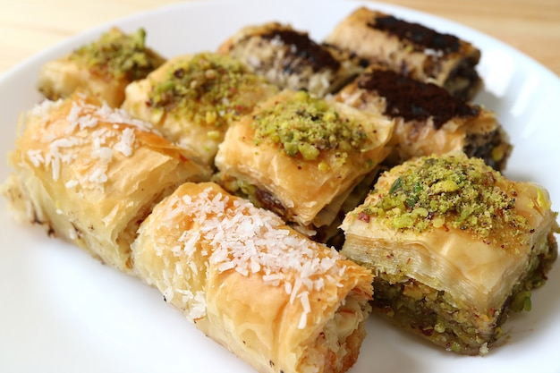 Different types of mouthwatering baklava pastries served on white plate