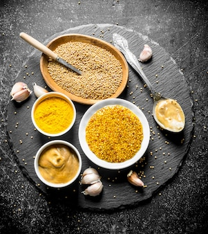 Different types of mustard on a stone board with garlic. on dark rustic table