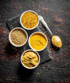 Different types of mustard on a stone board with a spoon. on dark rustic table