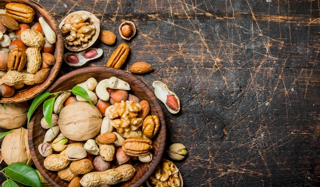 Different types of nuts in bowls with green leaves on wooden table.
