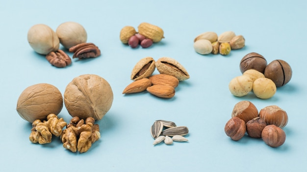Different types of nuts peeled and unpeeled on a blue background. vegetarian food.