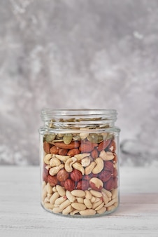 Different types of nuts and seeds in a glass jar close up