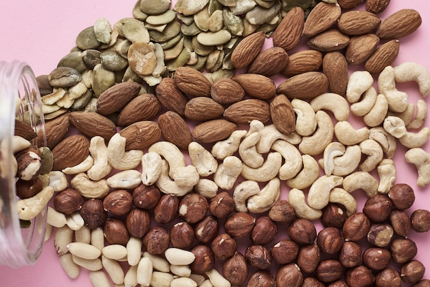 Different types of nuts and seeds in a glass jar on pink background, top view