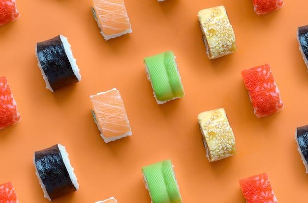 아시아 스시의 종류 오렌지 배경에 롤. 일식 미니멀리즘 평면도 평면 위치 패턴