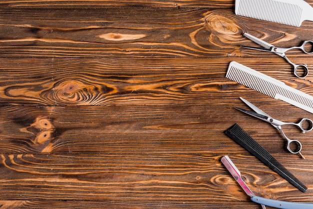 Различные типы парикмахерских инструментов в ряд на деревянной поверхности