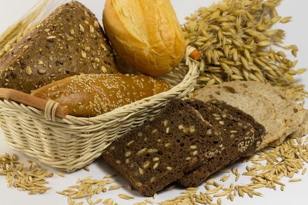 Хлеб разных сортов: белый и черный с семечками, багеты и булочки в плетеной корзине. зерна овса и веточки овса