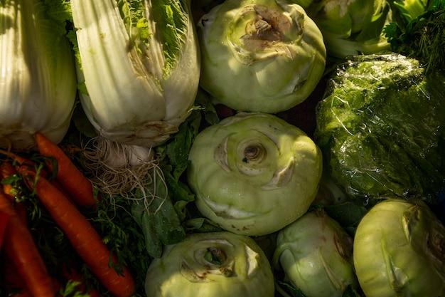 시장 카운터에 있는 다양한 종류의 양배추. 배추와 알 줄기 양배추입니다. 자연에서 온 건강과 비타민. 평면도.