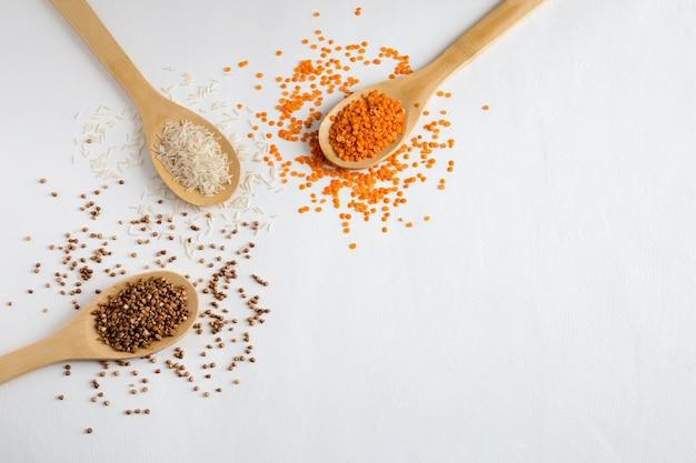 다른 유형의 곡물 메밀, 쌀 및 렌즈 콩 플랫은 복사 공간이있는 나무 숟가락에 놓여 있습니다.
