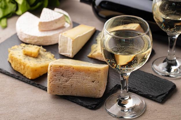 灰色のテーブルにさまざまな種類のチーズとワイン
