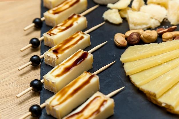 チーズメーカーからのプレゼンテーションでのさまざまな種類のチーズ。ブルーチーズ、ナッツとブリーチーズ、木製のテーブルの上の蜂蜜とチーズプレートの上面図。