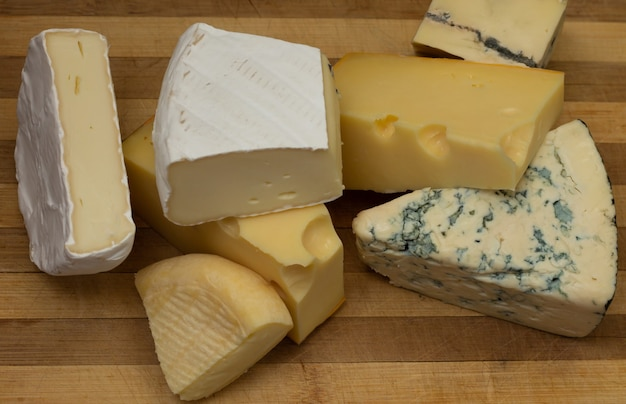 소박한 나무 커팅 보드에 있는 다양한 종류의 치즈. 평면도.