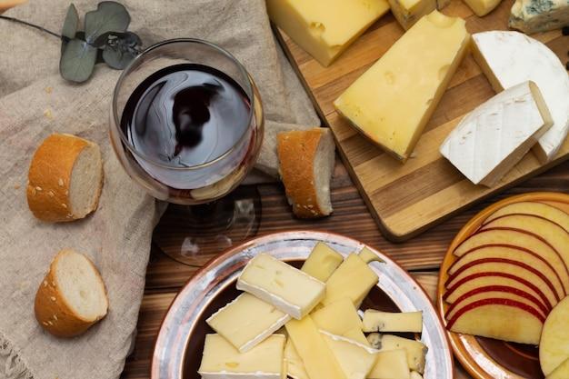 얇게 썬 사과와 와인 한 잔을 곁들인 소박한 나무 커팅 보드에 다양한 종류의 치즈가 있습니다. 평면도.