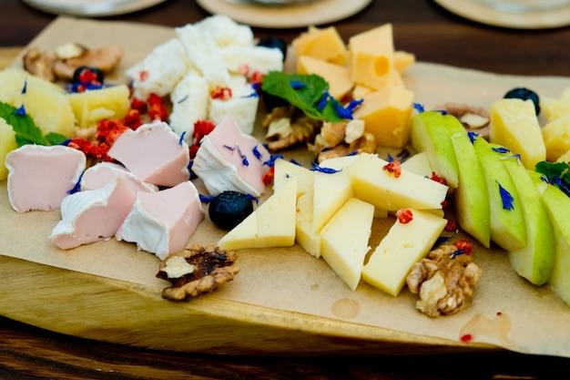 레스토랑에서 나무 접시에 사과와 견과류를 넣은 다양한 종류의 치즈. 확대.