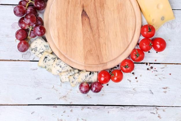 Различные виды сыра с пустой доской на крупном плане стола