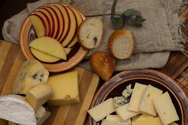 소박한 나무 커팅 보드에 얇게 썬 사과를 넣은 다양한 종류의 치즈. 평면도.