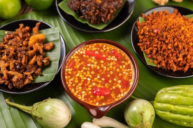 Различные виды соуса чили в чашке с ингредиентами для приготовления
