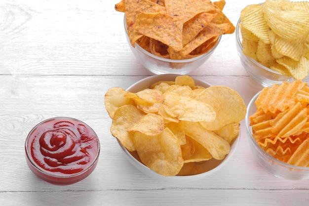 Различные виды чипсов в мисках и красном соусе