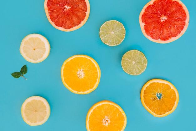 青い背景に柑橘類のスライスの異なるタイプ