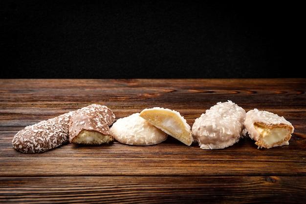 Различные виды печенья на столе из темного дерева.