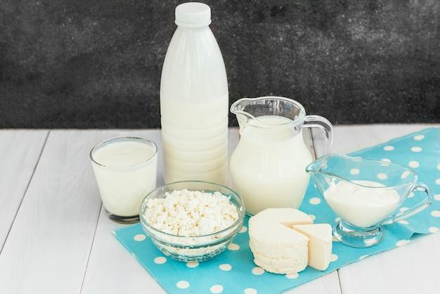Различные виды молочных продуктов на белом фоне деревянных.