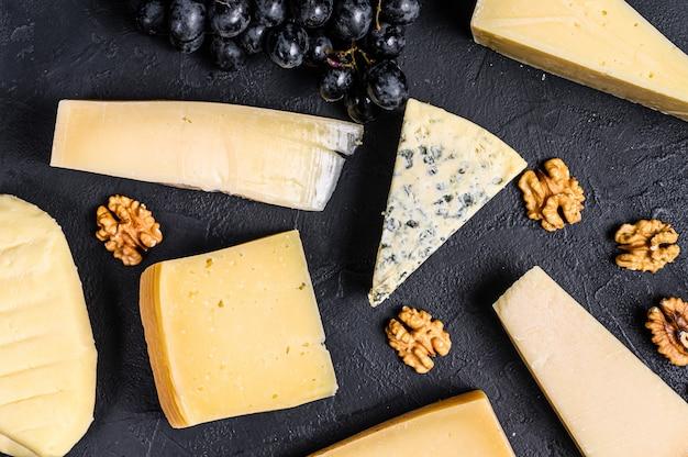 Различные виды вкусного сыра с грецкими орехами и виноградом. черная стена. вид сверху
