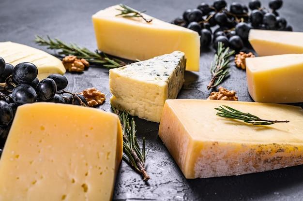 Различные виды вкусного сыра с грецкими орехами и виноградом. вид сверху