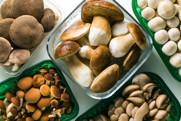 Различные виды свежих грибов в пластиковой упаковке, изолированные на белом столе