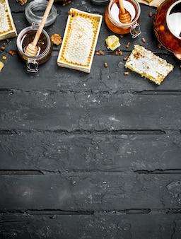 さまざまな種類の蜂蜜。黒い素朴なテーブルの上。