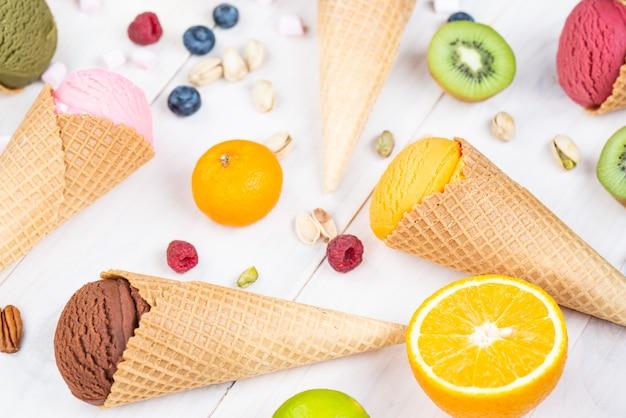 Различные виды мороженого с ягодами и фруктами на деревянном столе