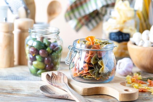 黄色の木製のテーブルの上のガラスの瓶でイタリアンパスタの種類。着色された自然なのり。ほうれん草、ビートルート、卵。セレクティブフォーカス