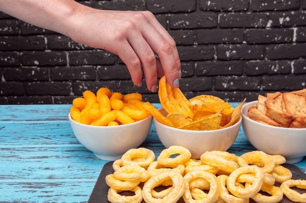 さまざまな種類のジャンクフード、塩味のスティック、木製のテーブルに塩味のクラッカー