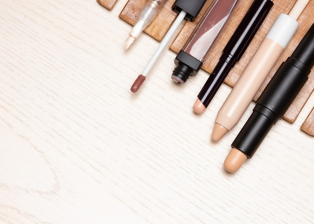 白い木のテーブルの上のさまざまなタイプの化粧コンシーラー上面図のコピースペース