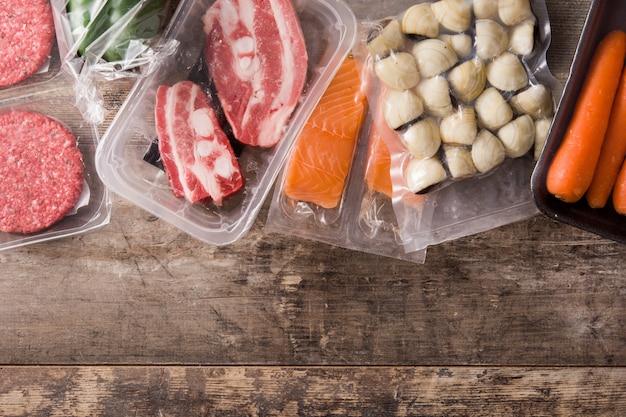 Различные виды мяса, овощей и морепродуктов на деревянном столе вид сверху копирование пространства