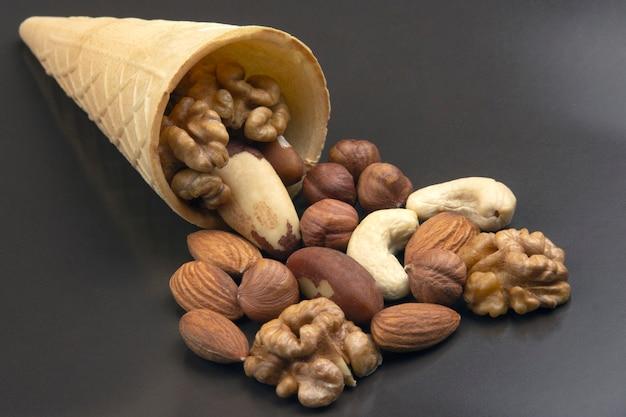 Различные виды орехов в вафельном рожке на серой поверхности. здоровая и белковая пища