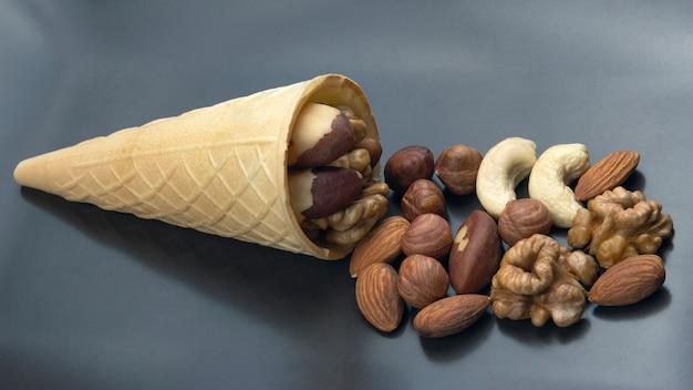 Различные виды орехов в вафельном рожке на сером