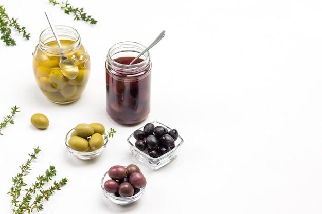 Различные виды оливок в стеклянных мисках и банках. веточки тимьяна на столе. вид сверху.