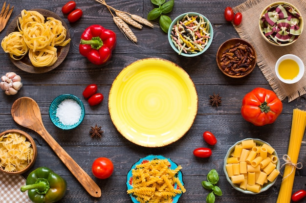 木製のテーブル、トップビューで野菜、健康またはベジタリアンの概念のさまざまな種類のパスタの種類