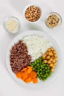 Different types of porridge with vegetables on plate with rice bowls