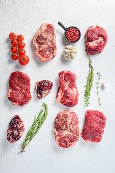 Различные виды сырых стейков из говядины на белом столе