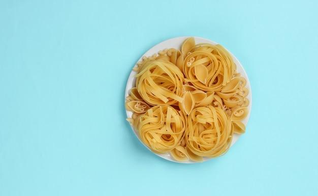 Различные виды сырых итальянских макарон в тарелке на синем фоне.