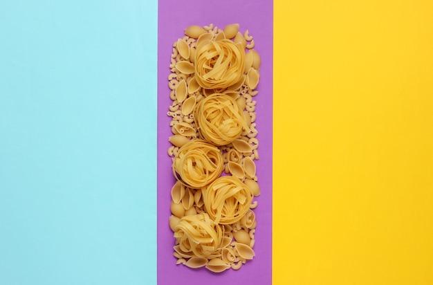 色付きの背景に生のイタリアンパスタのさまざまな種類。ミニマリズム食品のコンセプト。コピースペース