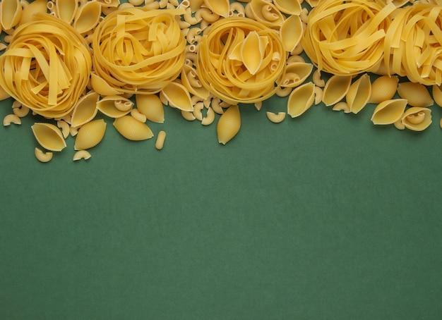 緑の背景に生のイタリアンパスタのさまざまな種類。上面図。コピースペース