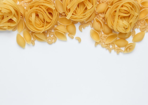 白い背景の上の生のイタリアンパスタのさまざまな種類。上面図。コピースペース