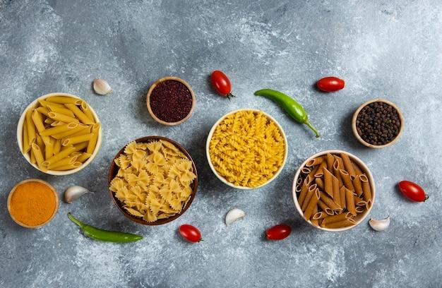 Различные виды сырых макарон и овощей.
